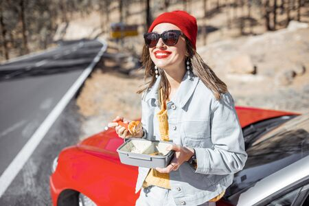 Woman having a snack with lunch box while standing on the roadside near the car, traveling on the mountains 免版税图像 - 139728019