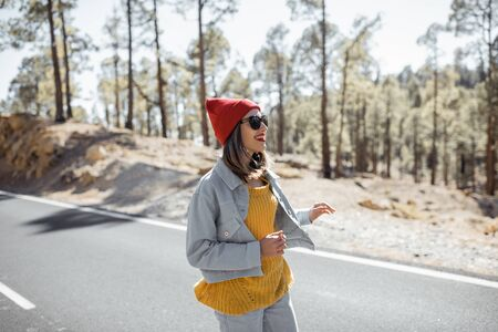 Lifestyle portrait of a stylish woman running on the beautiful mountain road, feeling happy and carefree while traveling 免版税图像 - 139728008