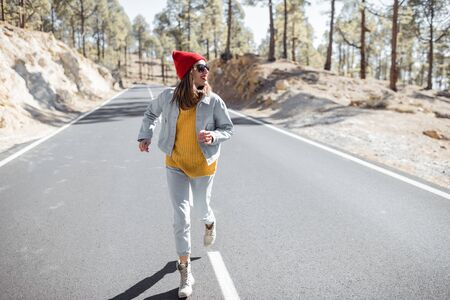 Lifestyle portrait of a stylish woman running on the beautiful mountain road, feeling happy and carefree while traveling Foto de archivo