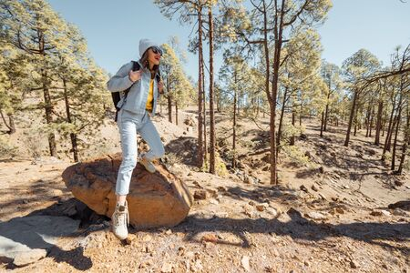 Young woman dressed casually walking with backpack in the forest highly in the mountains on the volcanic rocks, traveling on Tenerife island, Spain Zdjęcie Seryjne