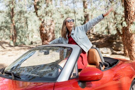 Young stylish woman enjoying traveling by convertible car on nature, pulling hands out of the car. Carefree lifestyle and travel concept