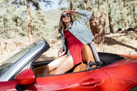 Young stylish woman enjoying traveling by convertible car on nature, looking out of the car in the forest. Carefree lifestyle and travel concept