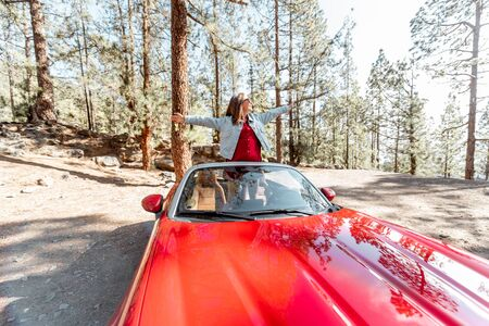 Young stylish woman enjoying traveling by convertible car on nature, pulling hands out of the car. Wide view