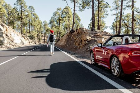 Carefree woman walking on the mountain road, traveling on a beautiful sports car