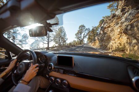 Woman driving car on the mountain road, close-up view with back focus on the road. Road trip concept
