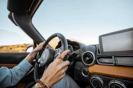 Woman driving car on the desert road, close-up view focused on the steering wheel and hands Stockfoto