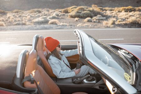 Woman driving convertible car while traveling on the desert road during a sunset. Carefree lifestyle and travel concept