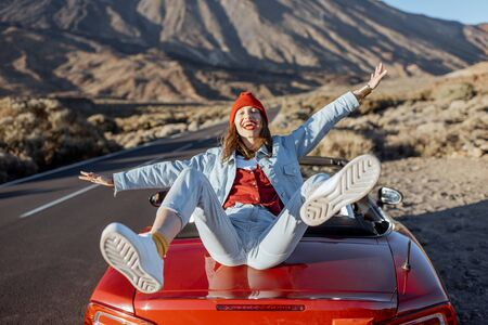 Lifestyle portrait of a joyful woman dressed casually enjoying road trip on the volcanic valley, traveling by car on Tenerife island