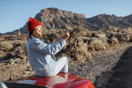 Woman enjoying beautiful rocky landscapes, sitting on the car hood on the roadside during a sunset. Traveling on the volcanic valley on Tenerife island