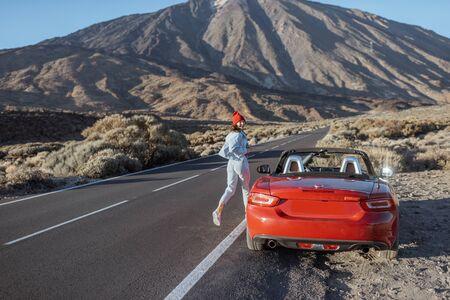 Młoda kobieta korzystających z podróży na zachód słońca, biegnie do samochodu na poboczu pięknej wulkanicznej doliny. Podróżowanie po Teneryfie