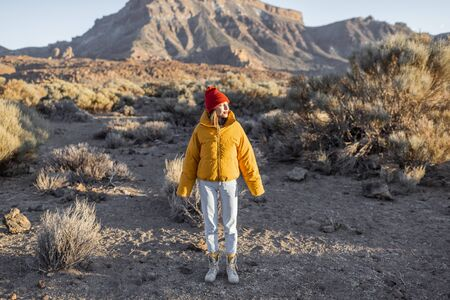 Woman in yellow jacket and red hat on the beautiful volcanic valley with mmountains on the background during a sunset. Traveling on Tenerife island, Spain