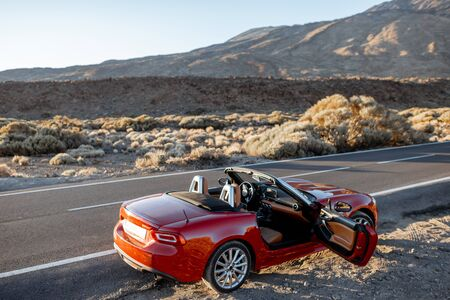 Convertible sports car on the roadside of the desert valley on a sunset