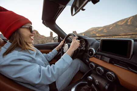 Happy woman in red hat driving convertible car while traveling on the desert road with beautiful rocky landscape on the background during a sunset