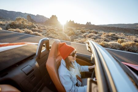 Happy woman in red hat driving convertible car while traveling on the desert road. Image focused on the rocks on the background