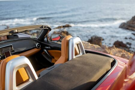 Convertible car on the rocky seaside, no people. Travel by car concept Archivio Fotografico