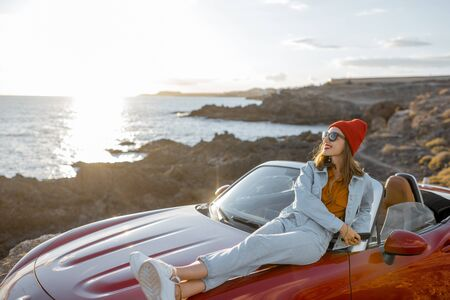 Young stylish woman enjoying beautiful landscapes, lying on the car hood while travel on the rocky coastline on a sunset. Carefree lifestyle and car travel concept