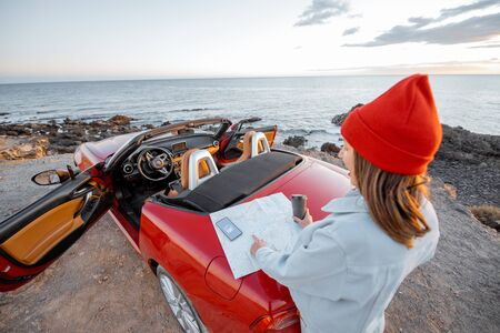 Woman traveling by car near the ocean, standing near the car trunk with paper map on the rocky coast during a sunset. Top view from the backside