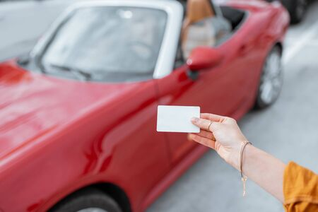 Woman holding plastic card with empty space to copy paste with red car on the background. Vehicle identification card concept