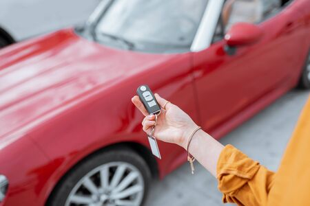 Woman holding keychain of a new purchased or leased red car at the parking place outdoors, close-up on hands and keys