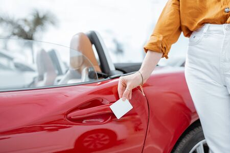 Woman opening car door with a plastic card, close-up on hands and door handle. Concept of keyless car access with a card