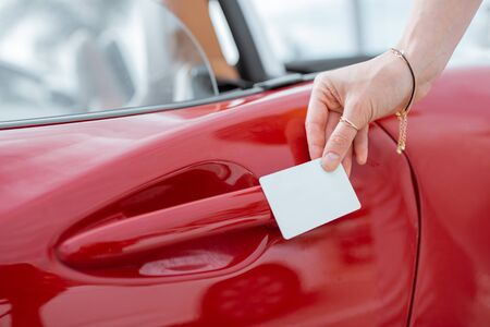 Woman opening car door with a plastic card, close-up on hands and door handle. Concept of keyless car access with a card 版權商用圖片