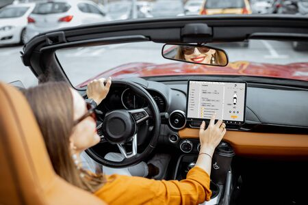 Cheerful woman controlling car with a digital dashboard, switching autopilot mode while driving a cabriolet. Smart car concept