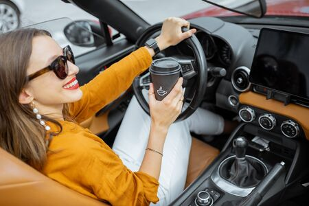 Portrait of a happy young woman driving sports car, enjoying roadtrip with a coffee cup
