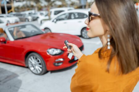 Young woman holding keychain of a new purchased or leased red car at the parking place outdoors