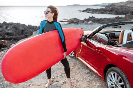 Portrait of a young woman surfer in swimsuit standing with surfboard near the car on the rocky coast. Active lifestyle and surfing concept