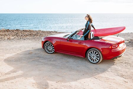 Young woman surfer driving red cabriolet with a surfboard on the rocky coast. Carefree lifestyle and active sports concept Stock Photo