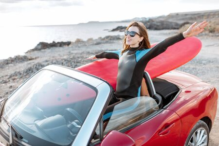 Young woman surfer driving red cabriolet with a surfboard on the rocky coast. Carefree lifestyle and active sports concept