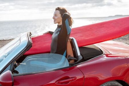 Young woman surfer driving red cabriolet with a surfboard on the rocky coast. Carefree lifestyle and active sports concept Archivio Fotografico