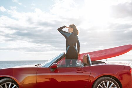 Woman enjoying beautiful landscapes while standing on her sports car with a surfboard near the ocean. Carefree lifestyle and active sports concept Standard-Bild
