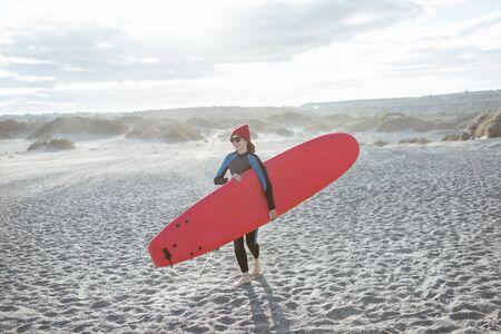 Surfeur de jeune femme en maillot de bain marchant avec une planche de surf rouge sur la plage venteuse. Concept de mode de vie actif et de surf