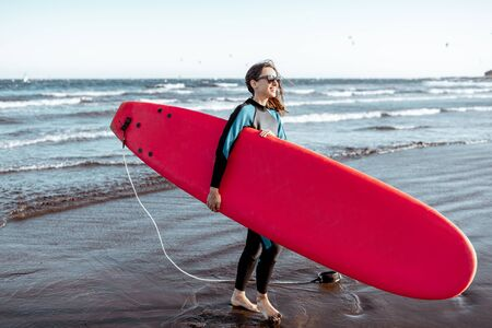 Portrait of a young woman surfer in swimsuit standing with red surfboard on the beach. Active lifestyle and surfing concept