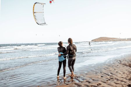 Couple of kitesurfers catching airflow with kite on the beach, view from the backside Stock Photo