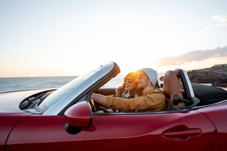 Joyful couple enjoying vacations, driving together convertible car near the ocean on a sunset. Happy vacation, love and travel concept