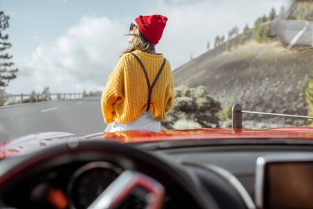 Lifestyle portrait of a carefree woman dressed casually in bright sweater and hat sitting on the car hood, enjoying road trip on the mountain road, view through the windshield