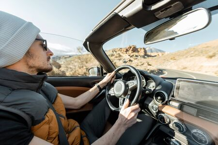 Man driving convertible car while traveling on the desert road. Carefree lifestyle and travel concept Archivio Fotografico