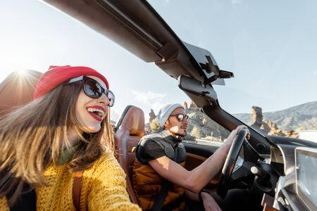 Selfie portrait of a happy couple while driving convertible sports car on the desert road during a sunset. Carefree lifestyle and travel concept 版權商用圖片
