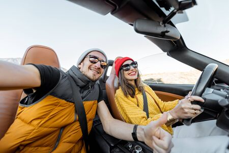 Selfie portrait of a happy couple while driving convertible sports car on the desert road during a sunset. Carefree lifestyle and travel concept Archivio Fotografico
