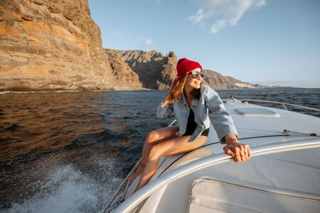 Young woman dressed casually in jacket and red hat enjoying sea voyage, sailing on a yacht in stormy ocean near a rocky shore. Extreme summer recreational pursuit Stock Photo