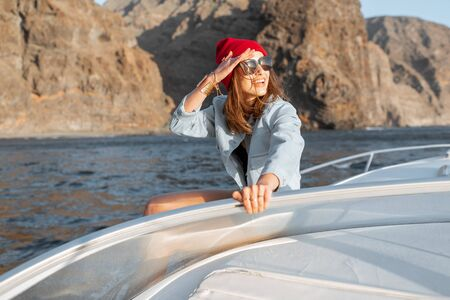 Woman dressed casually enjoying ocean voyage, sailing on a yacht near the breathtaking rocky coast on a sunset. Concept of a carefree lifestyle and travel Stock Photo