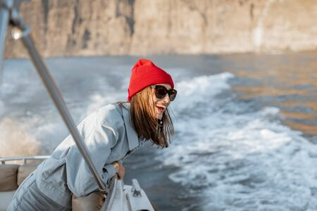 Portrait of a young woman traveler dressed casually in red hat and jeans sailing on a yacht near the rocky coast. Concept of a carefree lifestyle and travel