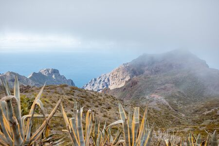 Beautiful landscape on a rocky mountain with the ocean on the background under the clouds, Tenerife island, Spain