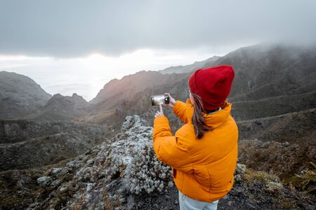 Young woman dressed in bright jacket and hat photographing on phone breathtaking views on the mountain range under the clouds, traveling on Tenerife island, Spain Stock Photo