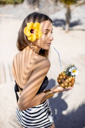 Portrait of a cute summer girl with exotic fruit and hair flower shaded with palm leaves on the sandy beach