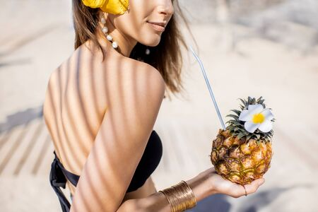 Portrait of a cute summer girl with exotic fruit shaded with palm leaves on the sandy beach