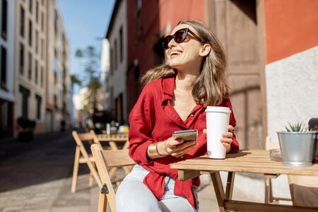Young woman enjoying a coffee, sitting with mobile phone on the cafe terrace on the old city street during a sunny day