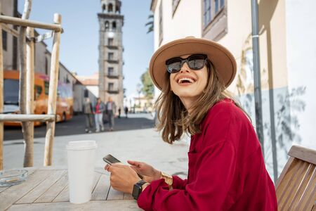 Young stylish woman feeling happy and calm, while resting on the cafe terrace in the old city street. Traveling in La Laguna city on Tenerife island
